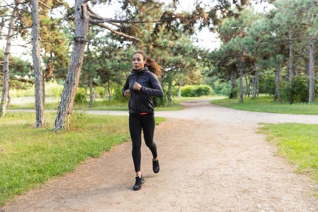Immagine di una giovane donna di 20 anni che indossa una tuta nera che si allena mentre corre attraverso il parco verde