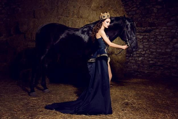 Immagine di una giovane donna vestita come una regina con un cavallo