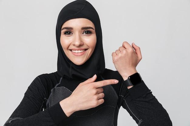 Immagine di giovane donna musulmana fitness utilizzando orologio orologio isolato.