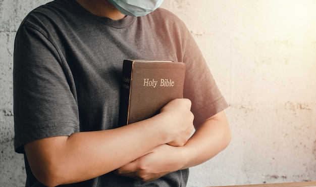 L'immagine di una giovane donna che tiene una bibbia stretta al petto. cristianesimo pronto a mostrare l'amore di dio