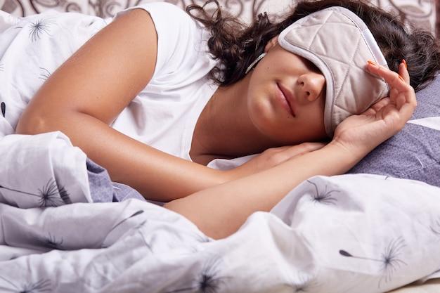 Immagine di giovane donna che dorme con la maschera per gli occhi, sdraiato sotto una coperta accogliente nel comodo letto di casa, signora bruna con i capelli ondulati