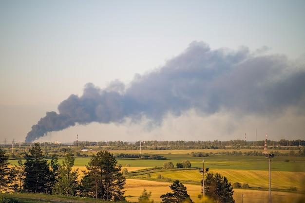 Immagini di fumo contro il cielo da un incendio in città all'orizzonte.