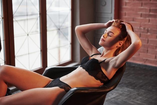 Immagina di essere in bagno. ragazza splendida calda in biancheria intima che si siede sulla sedia all'interno