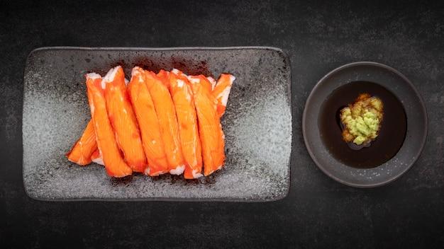 Bastoncini di granchio d'imitazione dell'alaska con salsa di soia wasabi e shoyu in piatto di ceramica su fondo di struttura di tono scuro, vista dall'alto