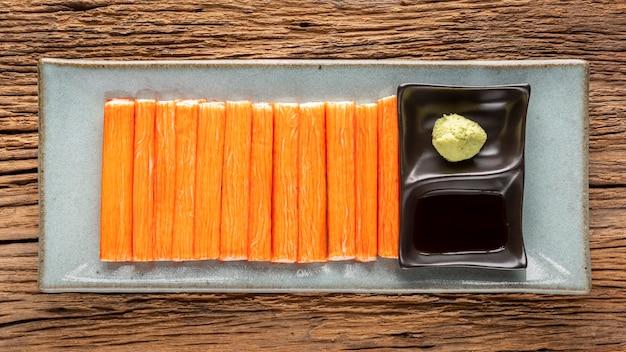 Bastoncini di granchio d'imitazione con wasabi e salsa di soia shoyu in piatto di ceramica su fondo rustico di legno naturale, vista dall'alto