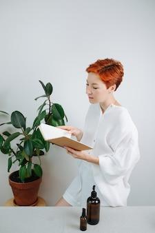 Donna immersa dai capelli corti che guarda il taccuino ecologico con una copertina di cartone. sta voltando pagine nere, fingendo di leggerlo.