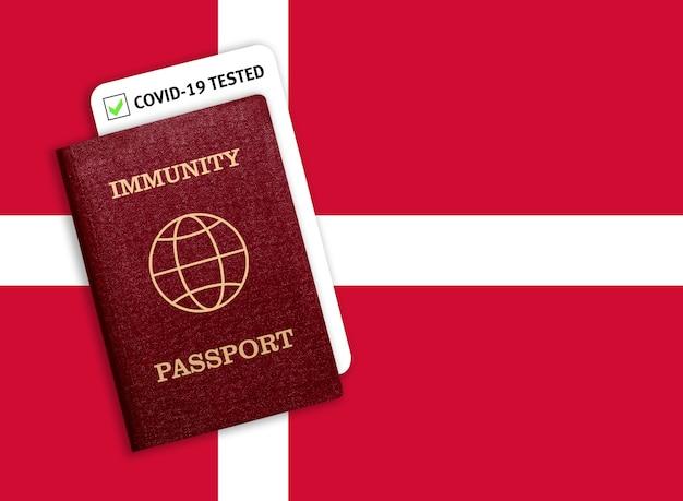 Passaporto di immunità sulla bandiera nazionale della danimarca