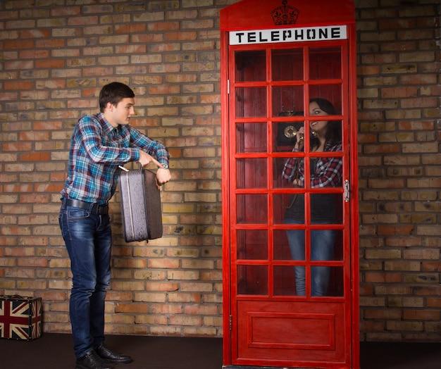 Uomo impaziente che indica il suo orologio mentre si trova accanto a una cabina telefonica britannica rossa con la sua valigia mentre sua moglie chiacchiera con gli amici al telefono