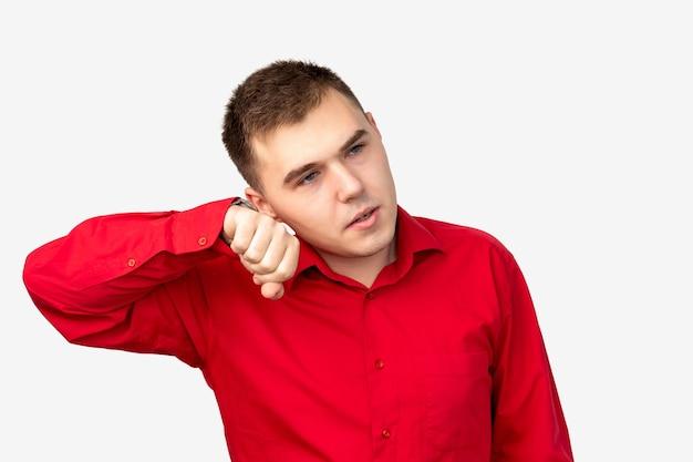 Ritratto di uomo impaziente. stress da ansia. ragazzo preoccupato in camicia rossa che ascolta l'orologio da polso isolato su bianco.