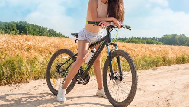 Ritratto impersonale di una donna in natura con una bicicletta. ricreazione e concetto di turismo. tecnica mista