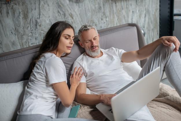 Informazioni importanti. uomo barbuto adulto preoccupato serio e giovane donna dai capelli lunghi con lo smartphone che esamina lo schermo del laptop