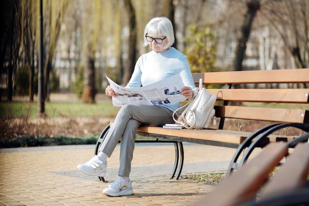 Notizia importante. grave donna invecchiata leggendo un giornale mentre è seduto sulla panchina