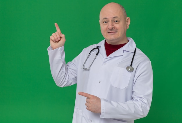Uomo adulto impressionato in uniforme del medico con lo stetoscopio rivolto verso l'alto e di lato