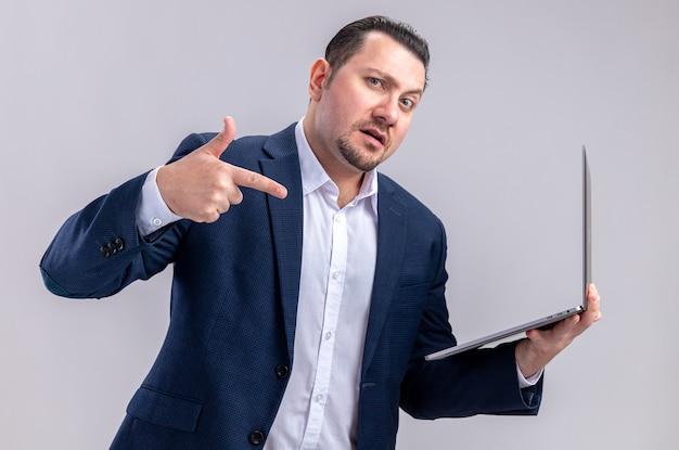 Impressionato uomo d'affari slavo adulto che tiene e punta al computer portatile isolato sul muro bianco con spazio copia