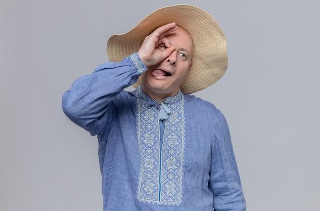 Impressionato uomo slavo adulto con cappello di paglia e camicia blu sporge la lingua e guarda di lato attraverso le dita