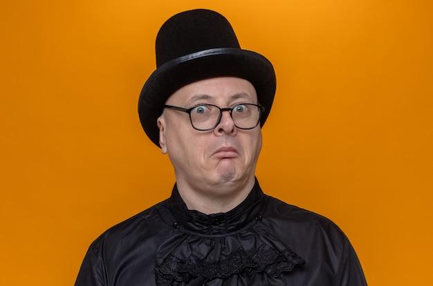 Impressionato uomo slavo adulto con cappello a cilindro e occhiali in camicia gotica nera