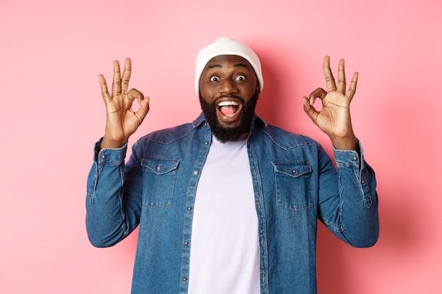 Impressionato uomo nero in berretto e camicia, che mostra segni ok e fissa la telecamera stupito, sorridendo felice, elogia la grande offerta, consiglia il prodotto, sfondo rosa