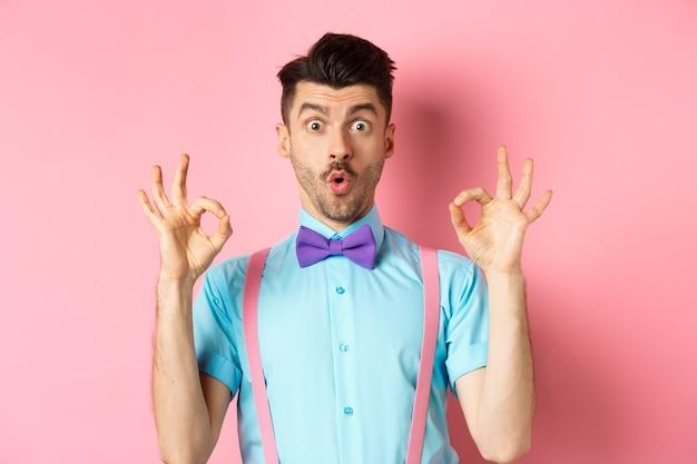 Ragazzo caucasico colpito in cravatta a farfalla, controllando un'offerta interessante, mostrando il gesto giusto e dicendo wow, lodando il buon prodotto, in piedi su sfondo rosa.
