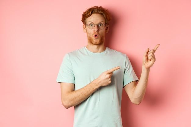 Ragazzo caucasico impressionato con barba e capelli rossi, puntando le dita nell'angolo in alto a destra e ansimante stupito, dicendo wow, in piedi su sfondo rosa.