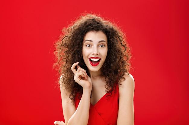 Donna adulta femminile impressionata ed eccitata con i capelli ricci in abito da sera rosso e elegante...