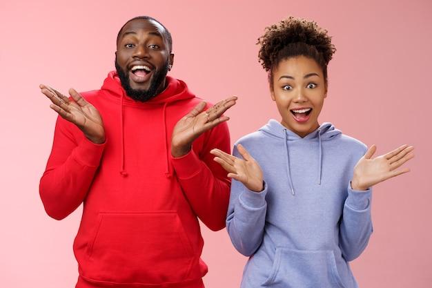 Impressionato felice entusiasta giovane coppia africano uomo donna relazione applaudendo le palme gioiosamente sorpresi occhi spalancati saluto con gioia gli amici che invitano a venire in ospitale, in piedi sfondo rosa