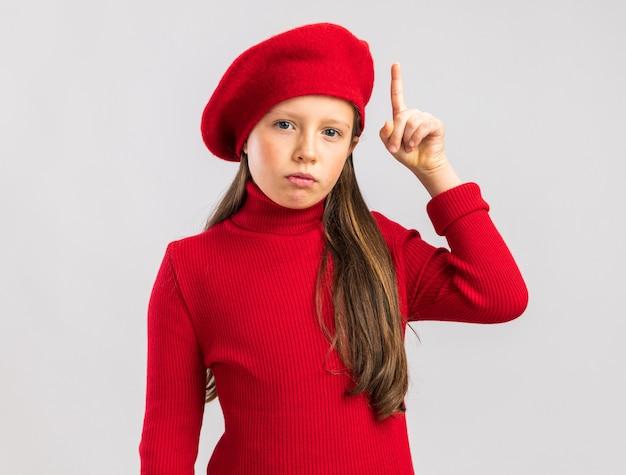 Piccola ragazza bionda impressionata che indossa il berretto rosso che indica in su isolato sul muro bianco