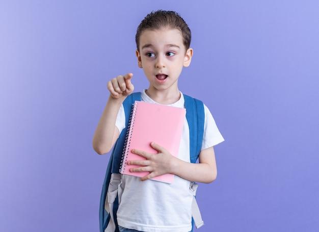 Impressionato ragazzino che indossa uno zaino che tiene il blocco note guardando il lato rivolto verso la telecamera isolata sulla parete viola con spazio per le copie