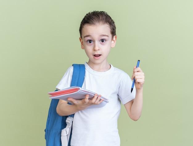 Impressionato ragazzino che indossa uno zaino che tiene un blocco note e una penna che guarda l'obbiettivo isolato sul muro verde oliva
