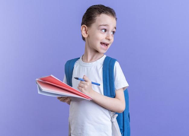 Impressionato ragazzino che indossa uno zaino in piedi in vista di profilo tenendo in mano penna e blocco note guardando il lato isolato sulla parete viola con spazio per le copie