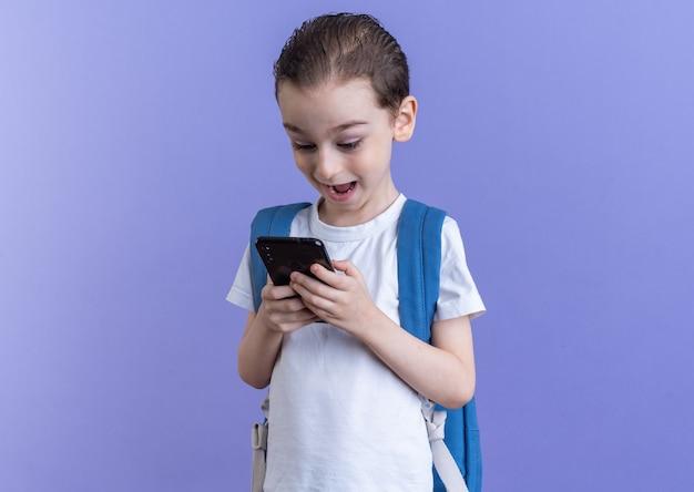 Ragazzino impressionato che indossa uno zaino utilizzando il telefono cellulare isolato sulla parete viola con spazio di copia