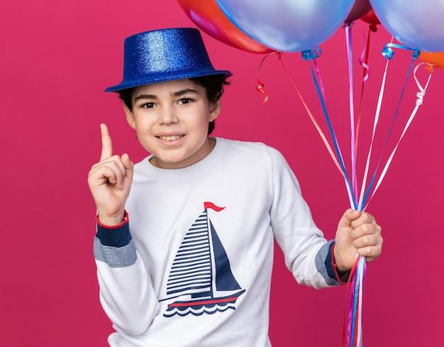 Il ragazzino impressionato che indossa il cappello da festa blu che tiene i palloncini punta verso l'alto isolato sul muro rosa