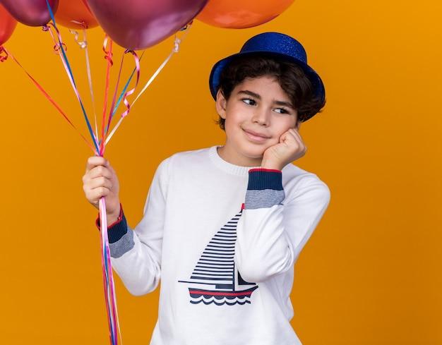 Impressionato ragazzino che indossa un cappello da festa blu con palloncini che mettono la mano sulla guancia isolata sul muro arancione