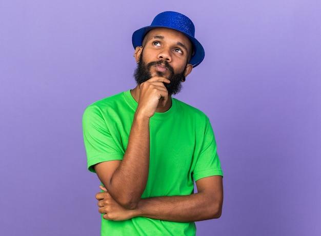 Impressionato guardando il giovane ragazzo afroamericano che indossa un cappello da festa ha afferrato il mento isolato sul muro blu