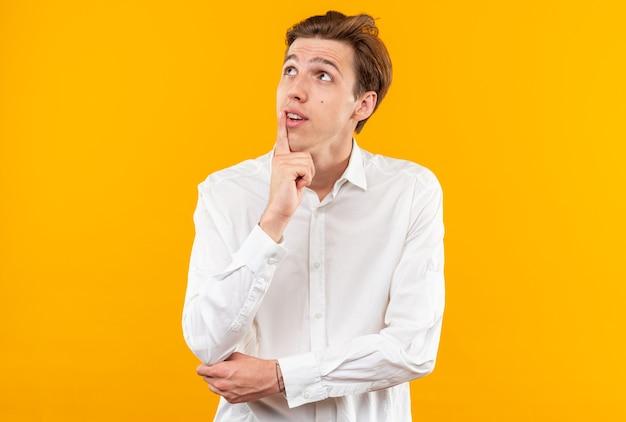 Impressionato guardando il giovane bel ragazzo che indossa una camicia bianca mettendo il dito sul mento