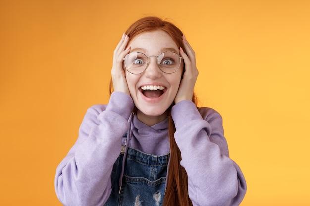 Impressionato fortunato ragazza rossa carina vincitrice non può credere che il sogno si avveri vinci un regalo fantastico in piedi felicemente eccitato afferra la testa sorridente bocca spalancata sguardo sorpreso stupito, sfondo arancione