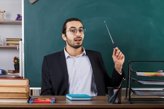 Insegnante maschio impressionato che indossa occhiali punti con puntatore stick alla lavagna seduto al tavolo con strumenti scolastici in classe