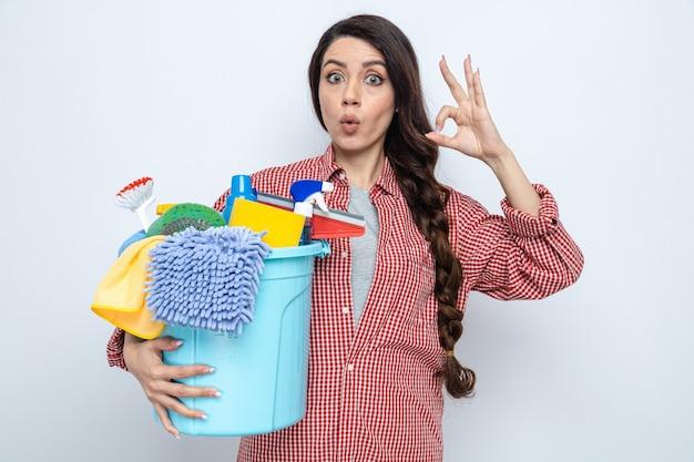 Impressionata donna delle pulizie piuttosto caucasica che tiene in mano l'attrezzatura per la pulizia e che fa un gesto ok segno