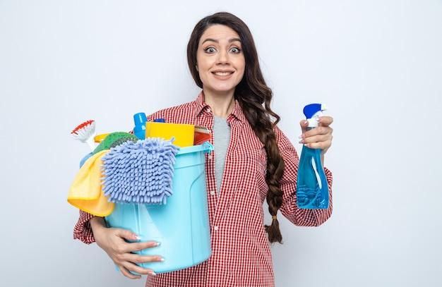 Impressionata donna abbastanza caucasica delle pulizie che tiene in mano attrezzature per la pulizia e detergente spray
