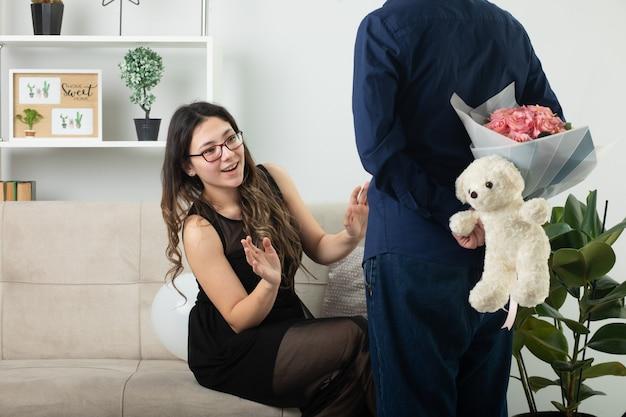 Impressionata bella giovane donna seduta sul divano e guardando un bell'uomo che nasconde un mazzo di fiori con un orsacchiotto in soggiorno