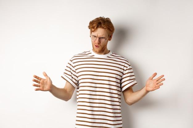 Uomo rosso impressionato con gli occhiali che mostrano la lunghezza di qualcosa di grande, dimostrano grandi dimensioni e guardando verso il basso, in piedi su sfondo bianco.