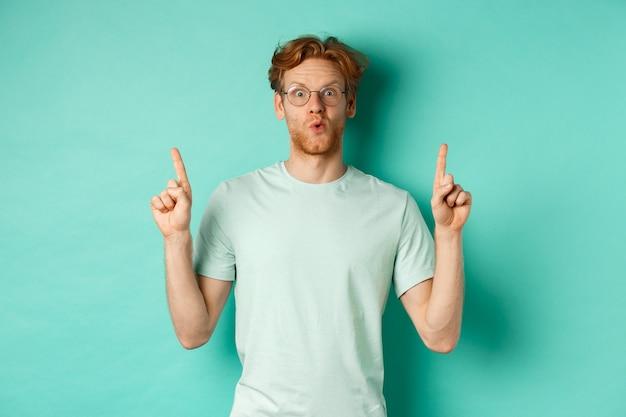 Uomo rosso impressionato con occhiali e t-shirt, controllando l'offerta promozionale, puntando le dita verso lo spazio della copia, fissando la telecamera stupito, in piedi su uno sfondo turchese.