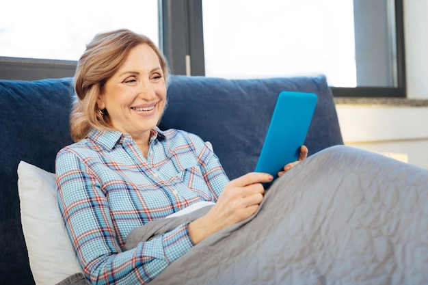 Impressionato dalle informazioni. curiosa donna anziana seduta da sola a letto e guardando sullo schermo del suo cellulare mobile