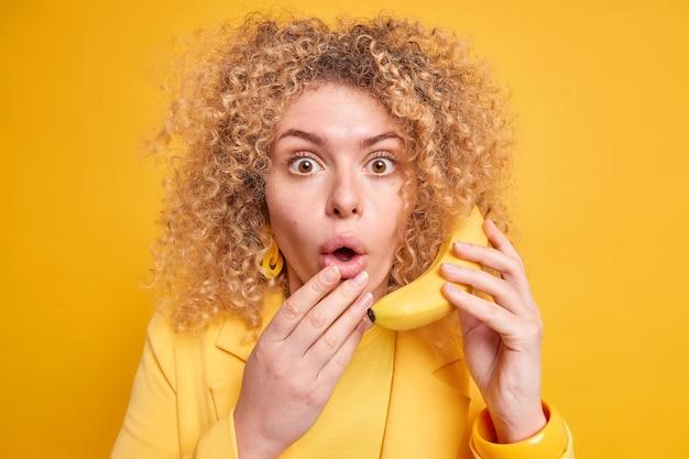 La donna impressionata con la pelle sana i capelli ricci e folti tiene la bocca aperta dallo stupore tiene la banana matura vicino all'orecchio finge che la conversazione telefonica indossa vestiti gialli in un tono con il muro