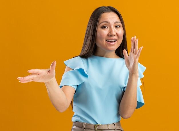 Impressionata giovane ragazza asiatica che guarda la telecamera tenendo le mani in aria spiegando qualcosa di isolato sulla parete arancione con spazio per le copie Foto Premium