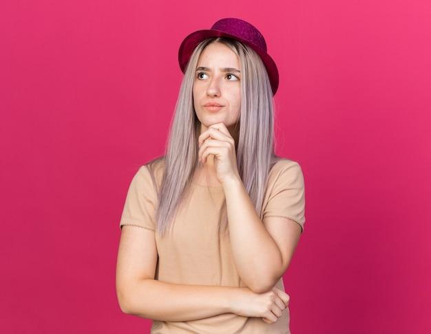 Colpito giovane bella donna che indossa il cappello da festa afferrò il mento isolato sulla parete rosa