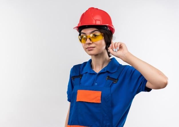 Impressionato giovane donna costruttore in uniforme con gli occhiali mettendo il dito sull'orecchio isolato sul muro bianco