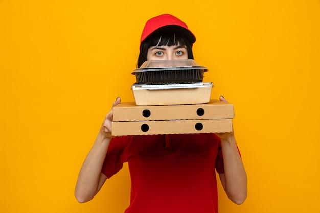 Colpita giovane ragazza delle consegne caucasica che tiene in mano contenitori per alimenti con imballaggi su scatole per pizza