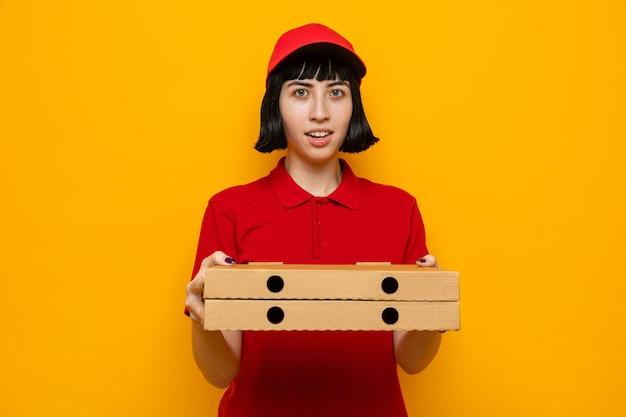 Colpita giovane donna di consegna caucasica che tiene scatole per pizza