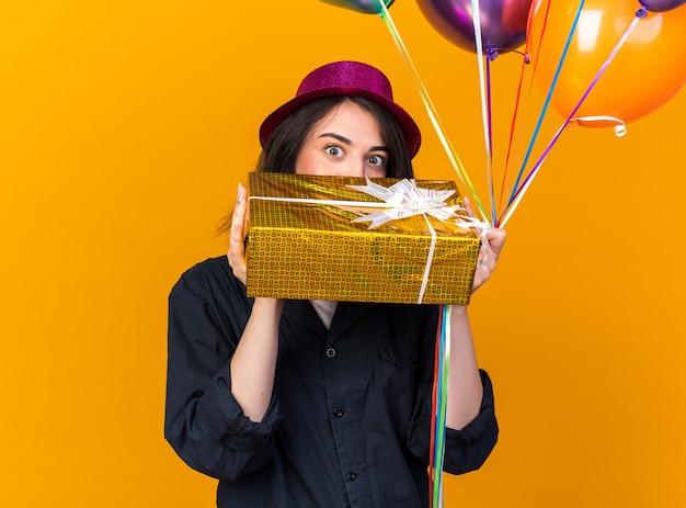 Impressionato giovane ragazza caucasica che indossa un cappello da festa con un mazzo di palloncini e un pacchetto regalo da dietro il pacchetto isolato su una parete arancione