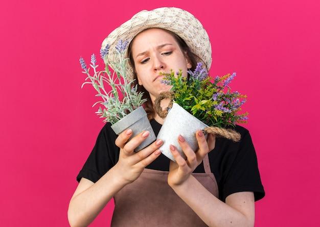 Impressionato giovane giardiniere femminile che indossa un cappello da giardinaggio che tiene e guarda i fiori in vasi da fiori isolati su una parete rosa
